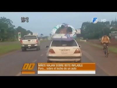 Niños viajan en un inflable sobre el techo de un vehículo