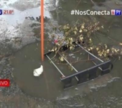 Aguas negras y baches inundan transitada calle de Asunción