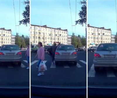 Un transeúnte pasó a través de un auto estacionado en un cruce peatonal.