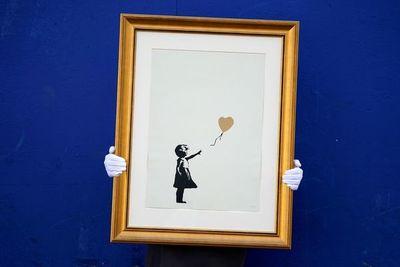 Varias fotografías retratan a un Banksy sin rostro trabajando en sus murales