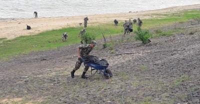 Milicos limpian basura que dejó el agua del río