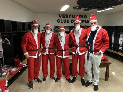 Vestidos de Papá Noel, ídolos de Olimpia llevan regalos a niños